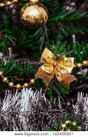 Christmas decorations on a green artificial fir. Golden bow. Photo with limited depth of field.