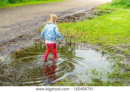 Little toddler girl with blonde pigtails en red boots walking through the water in the puddle. By playing in this way she discovers the world gradually.