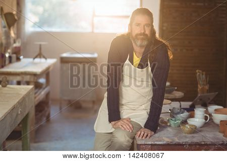 Portrait of male potter sitting on table in pottery workshop
