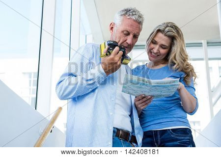 Low angle view of mature couple reading map at home
