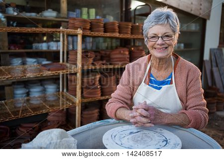 Portrait of female potter smiling in pottery workshop