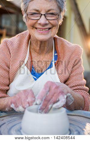 Portrait of female potter making pot in pottery workshop
