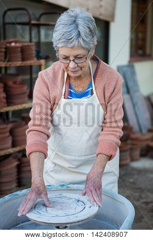 Female potter checking pottery wheel in pottery workshop
