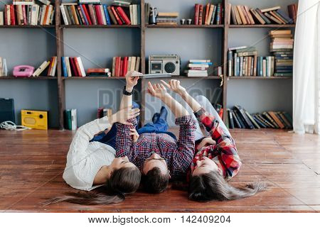 Three friends holding tablet at the floor.