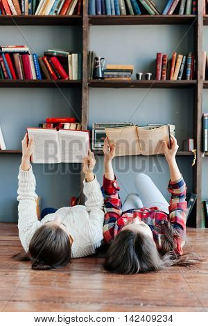 Students are laying on the floor and using books while working together at homework. Education concept.
