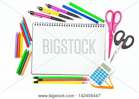 Notebook colored pencils crayons markers ballpoint pens and scissors isolated on white background