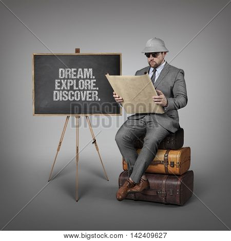 Dream. Explore. Discover. text on  blackboard with explorer businessman sitting on suitcases