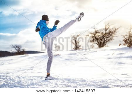Fit Man Practicing A Kick Shot Outdoor In Snow. Fitness Player Training And Practicing Outside On A