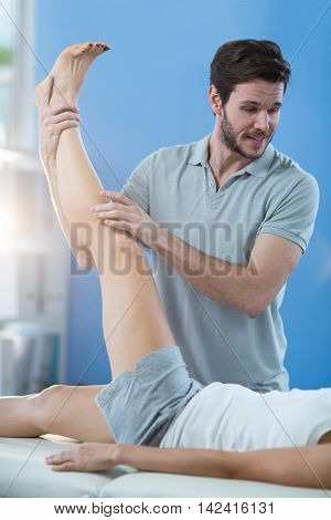 Male physiotherapist giving knee massage to female patient in clinic