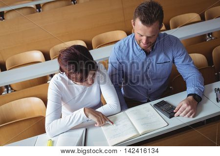 Mature students reading a book in the classroom