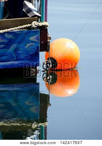 Orange Buoy Next To A Blue Boathouse In Victoria Harbor