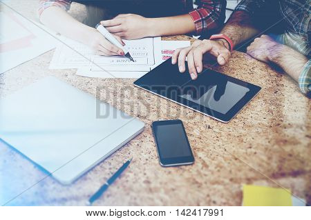 Businessman touching tablet screen. Businesswoman taking notes. Concept of working together. Toned image