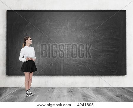 Young woman standing near blackboard holding tablet. Concept of studying at modern establishment. Mock up