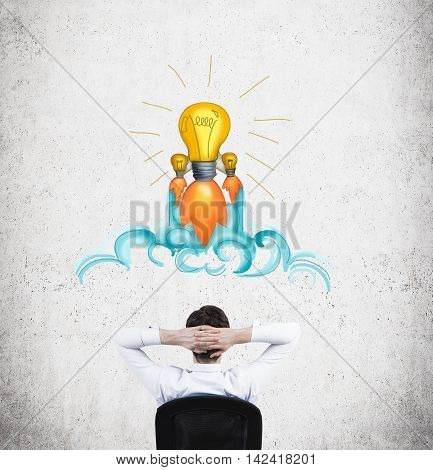 Businessman sitting in armchair with his back to camera in front of concrete wall with light bulb sketch on it thinking about business development. Concept of decision making and coming to conclusion