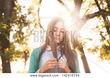 Young brunette in a shirt standing in front of the sun