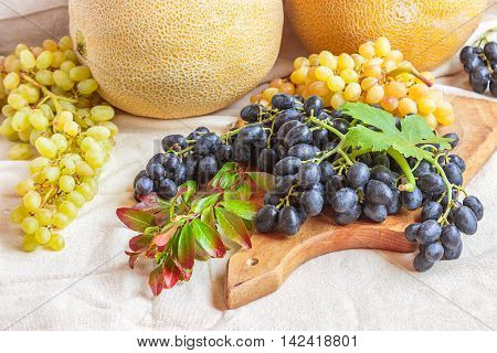 Still life - bright fruit on light fabric. Vintage black and green grapes melon and pomegranate branch. Concept - healthy food.