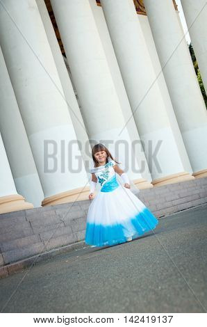 Little girl fashionista in an evening dress is standing near colonnade