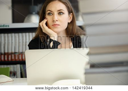 Attractive Student Girl With Confused Face Expression Sitting At Table At College Library, Working O