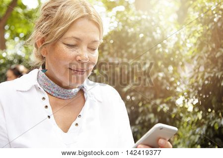 Portrait Of Beautiful 60-year Old Lady Using Wireless Internet Connection While Reading News On Her