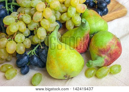 Still life - bright fruit on light fabric. Vintage black and green grapes fragrant pear. Concept - healthy food.