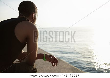 Back Shot Of African Athlete Wearing Sleeveless Top Relaxing After Outdoor Activity, Getting Ready F