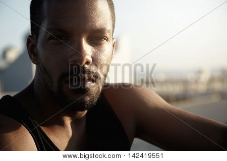Handsome Dark-skinned Tired Male Jogger Having Rest On Riverside After Every Morning Outdoor Workout