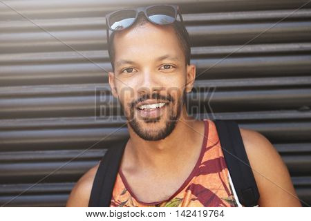 Attractive Dark-skinned Male Student With Sunglasses On His Head Looking At Camera, Having Joyful An