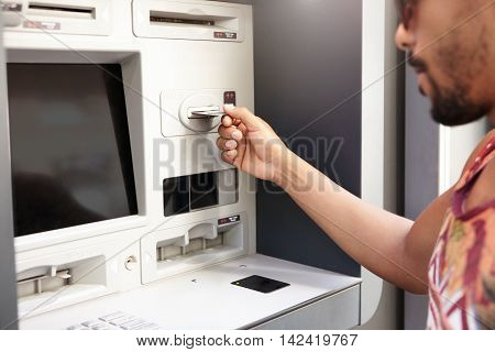 Human And Technology. Dark Skinned Man Using Atm. Black Guy's Hand Inserting Plastic Bank Card Into