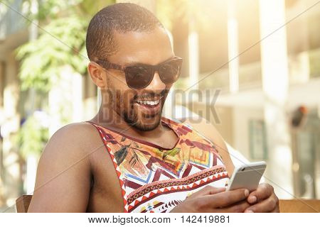 Young Attractive Dark-skinned Male Looking Happy Holding His Cellphone, Receiving Good News From Sis