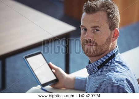 Portrait of mature student holding digital tablet in the classroom