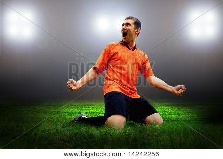 Futbolista de felicidad después del gol en la cancha del estadio con la luz