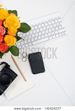 Feminine desk workspace with roses, computer keyboard, retro camera and notepad on white background. Startup concept, top view mockup.
