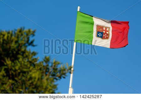 Italian flag with emblem of the four Maritime Republics Venice Genoa Pisa and Amalfi on a blue sky