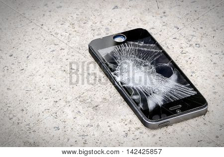 Smartphone with broken screen on the ground.