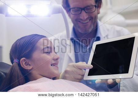 Dentist showing digital tablet to young patient in dental clinic