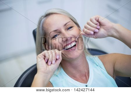 Woman flossing her teeth in dental clinic