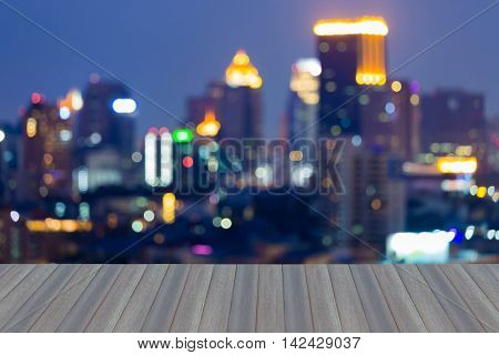 Opening wooden floor, abstract blurred lights urban office building at twilights