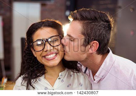 Man kissing woman on cheek in office