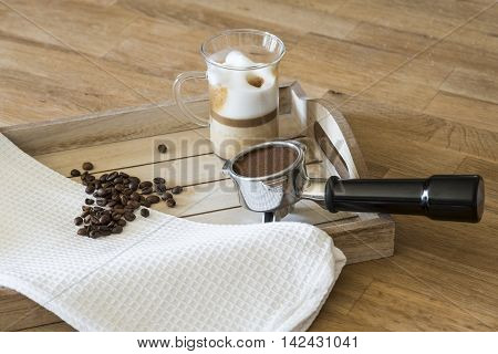 Glass of latte macchiato, coffee beans and a grouphead on a wooden tray