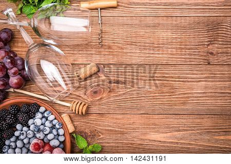 Homemade red wine sangria with fresh berries on a wooden table.