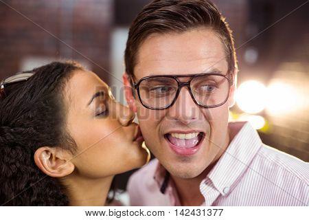 Woman kissing man on cheek in office