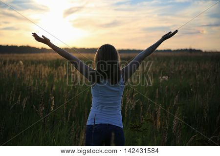 Young girl raises his hands with joy. Wheat field. Sunset. Evening