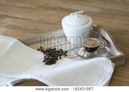 Glass of espresso, brown sugar, coffee beans and sugar bowl on a wooden tray