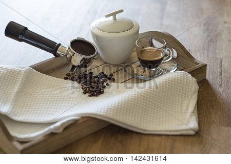 Glass of espresso, brown sugar, coffee beans, grouphead and sugar bowl on a wooden tray