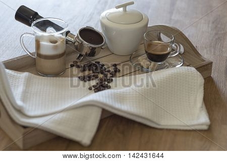 Wooden tray with glass of latte macchiato, espresso, grouphead, coffee beans and brown sugar