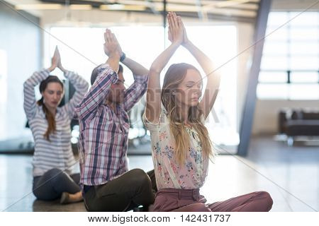 Business people performing yoga on floor in office
