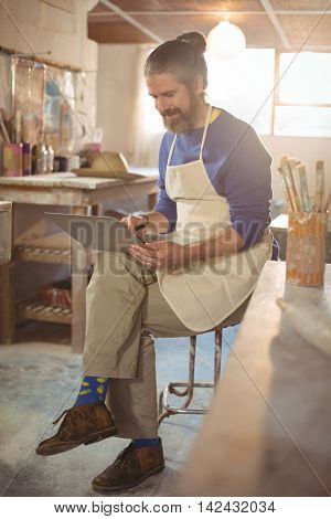 Male potter sitting on stool using laptop in pottery workshop