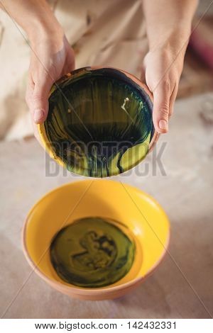 Close-up of potter pouring watercolor in bowl in pottery workshop