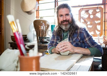 Portrait of male potter molding clay in pottery workshop