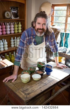 Portrait of male potter standing at table in pottery workshop
